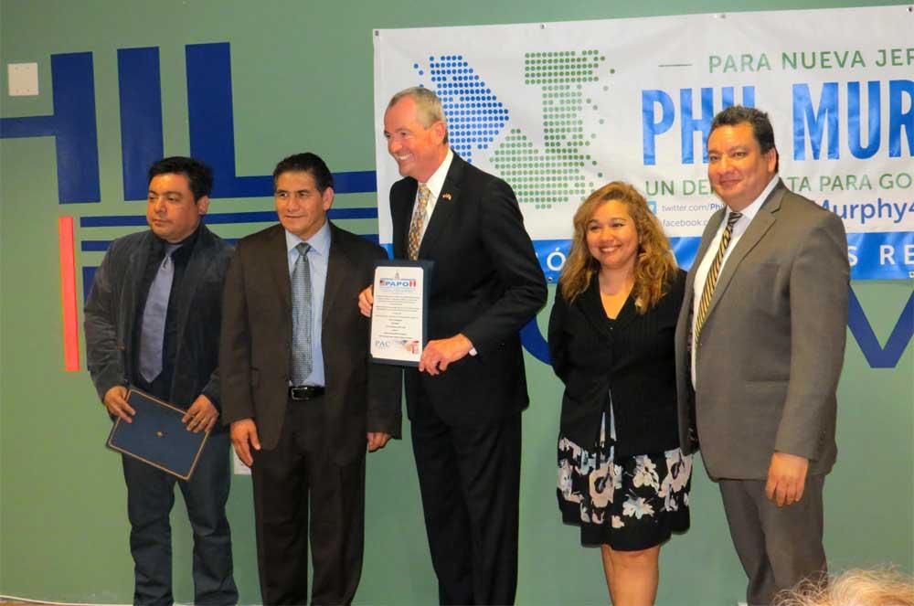 Norberto Curitumai, de la organización peruana PAC, entrega un pergamino al candidato Murphy, y le ofrece su respalgo político.